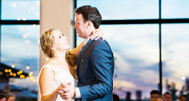 A BRIDE AND GROOM ENJOY FLOOR-TO-CEILING SUNSET VIEWS FROM THE BALLROOM AT UNIVERSITY CLUB