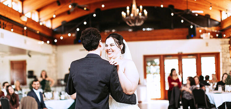 A NEW BRIDE SHARES A FIRST DANCE WITH HER HUSBAND IN THE BALLROOM AT OCOTILLO OASIS