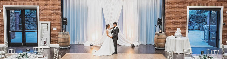A NEWLYWED COUPLE ENJOY AN INTIMATE MOMENT ALONE IN THE BALLROOM AT EVERGREEN SPRINGS