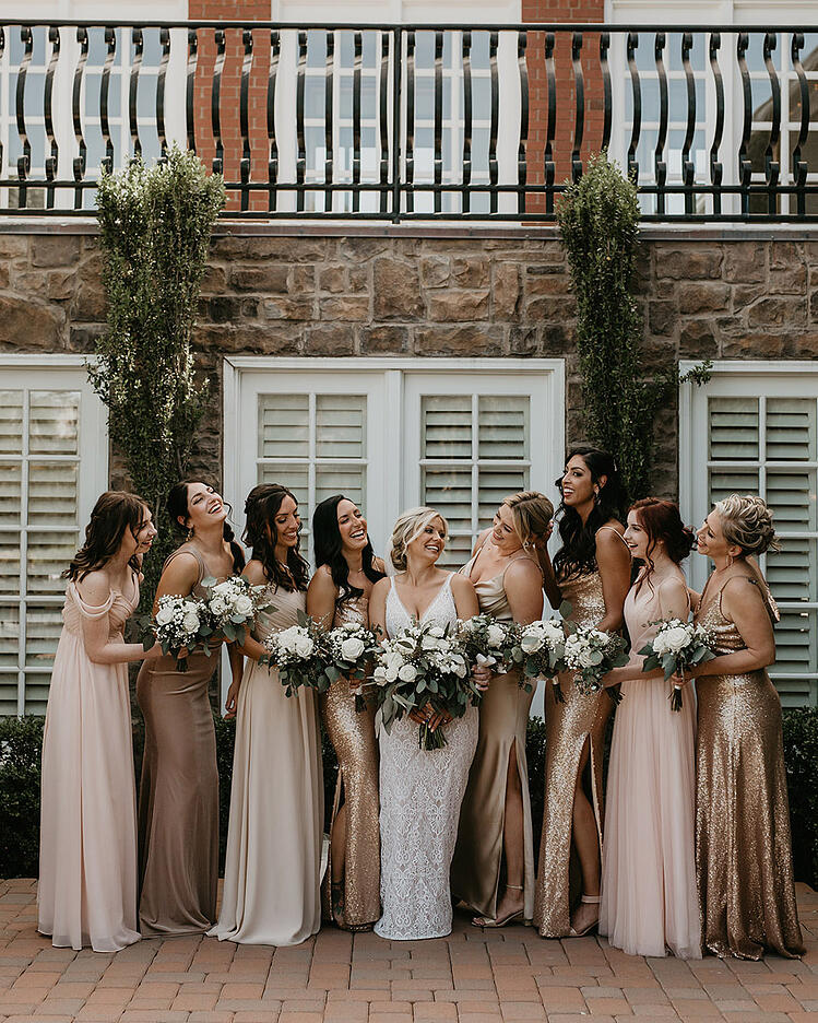 The bridal party sported beautiful mismatched dresses in gold, blush, and beige