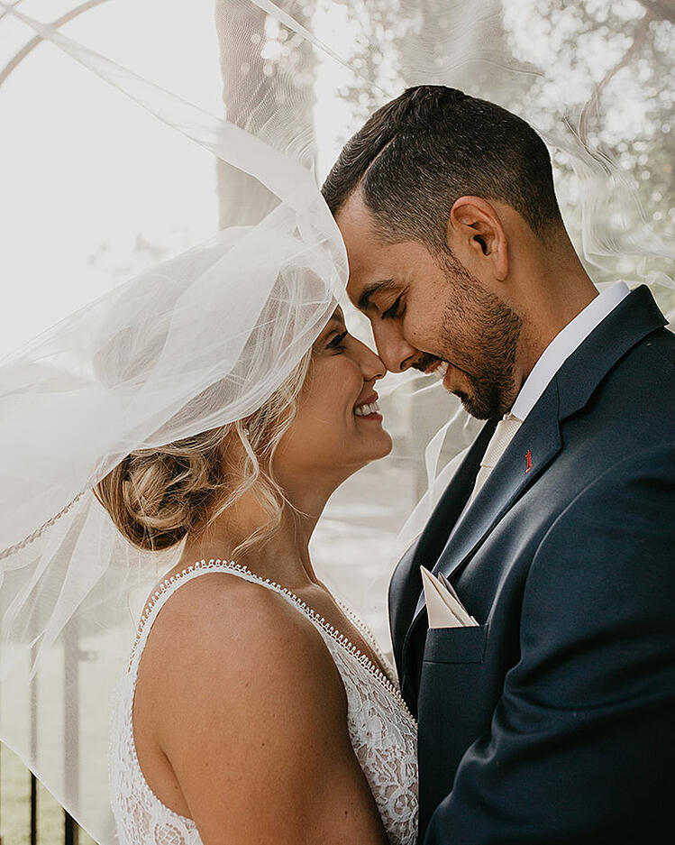 Lindsey & Marcos cocoon together under the billowing veil