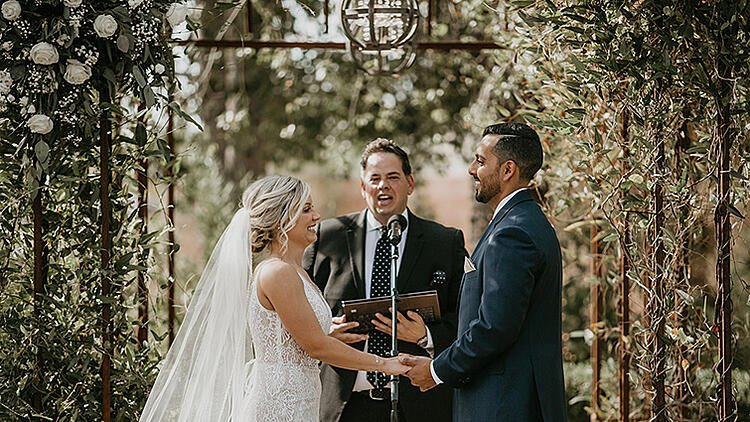 a heartfelt ceremony under the iron arbor decorated with white roses and ivy