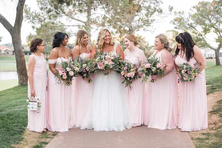 a bride and her bridesmaids in blush pink gowns at an outdoor garden wedding ceremony