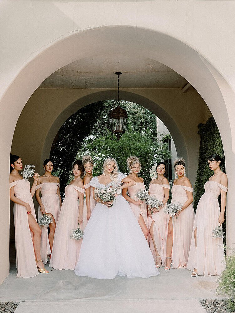 How dashing is this wedding party? The blush-colored gowns perfectly mesh with the black and white tuxedos and coordinating pink socks.