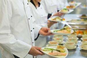 Chef holding salmon dishes standing in a row with colleagues-1