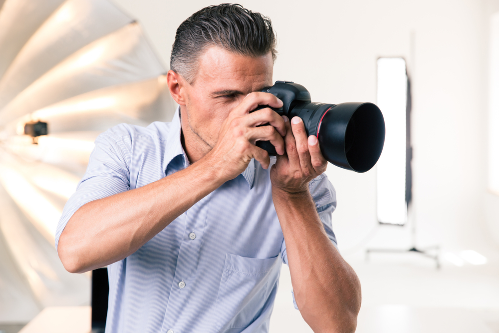 Handsome photographer making photo on camera in studio