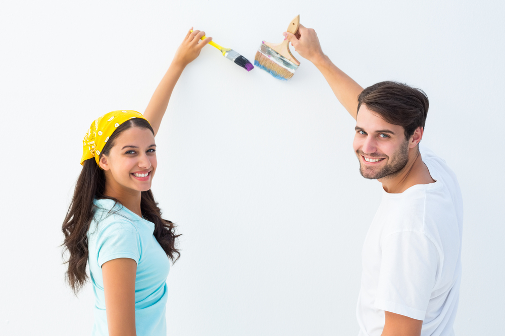 Happy young couple painting together on white background