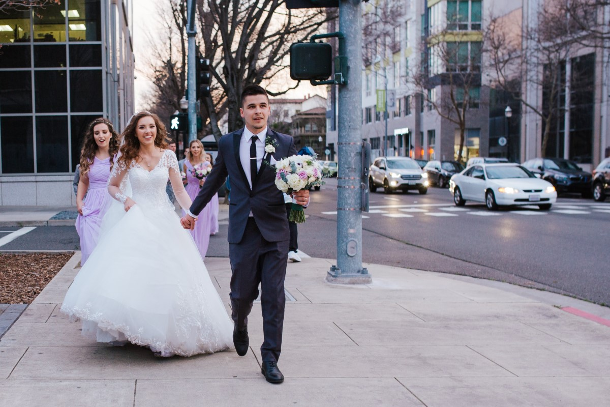 A bride and groom head to their Downtown Sacramento wedding venue at Sterling Hotel