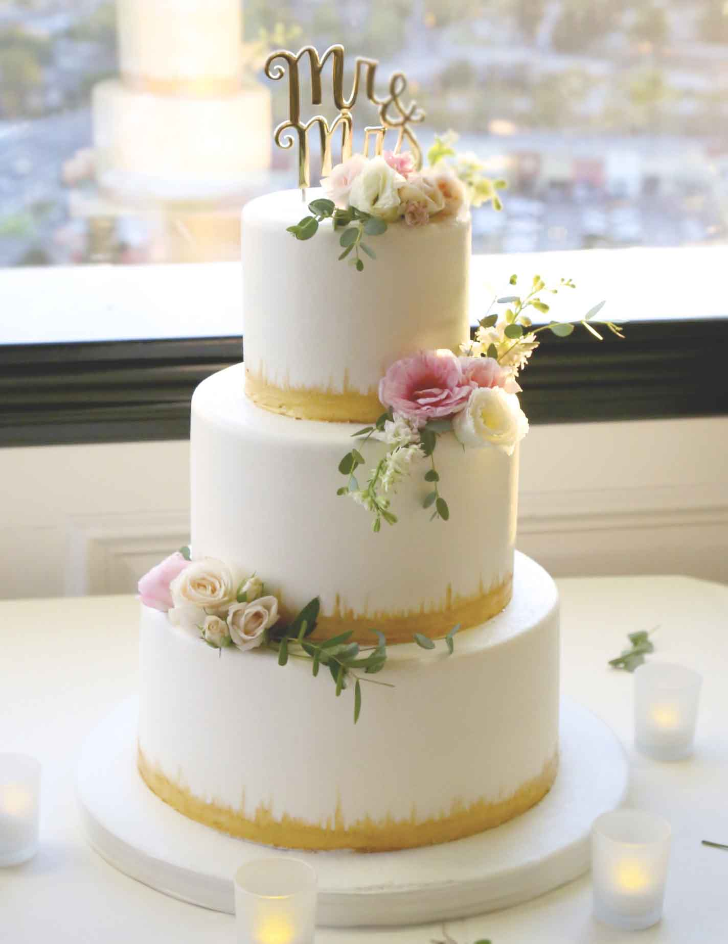 Lillian and Josh's three-tier wedding cake featured gold accents and pink roses