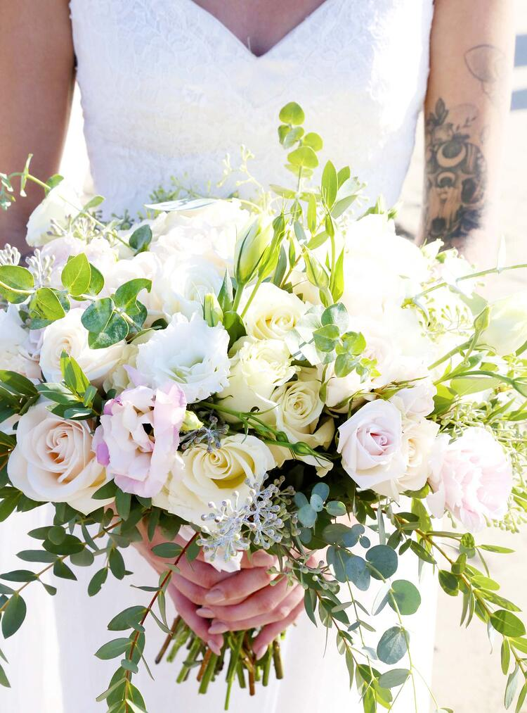Lillian carried a lush bouquet of soft roses and bright greenery