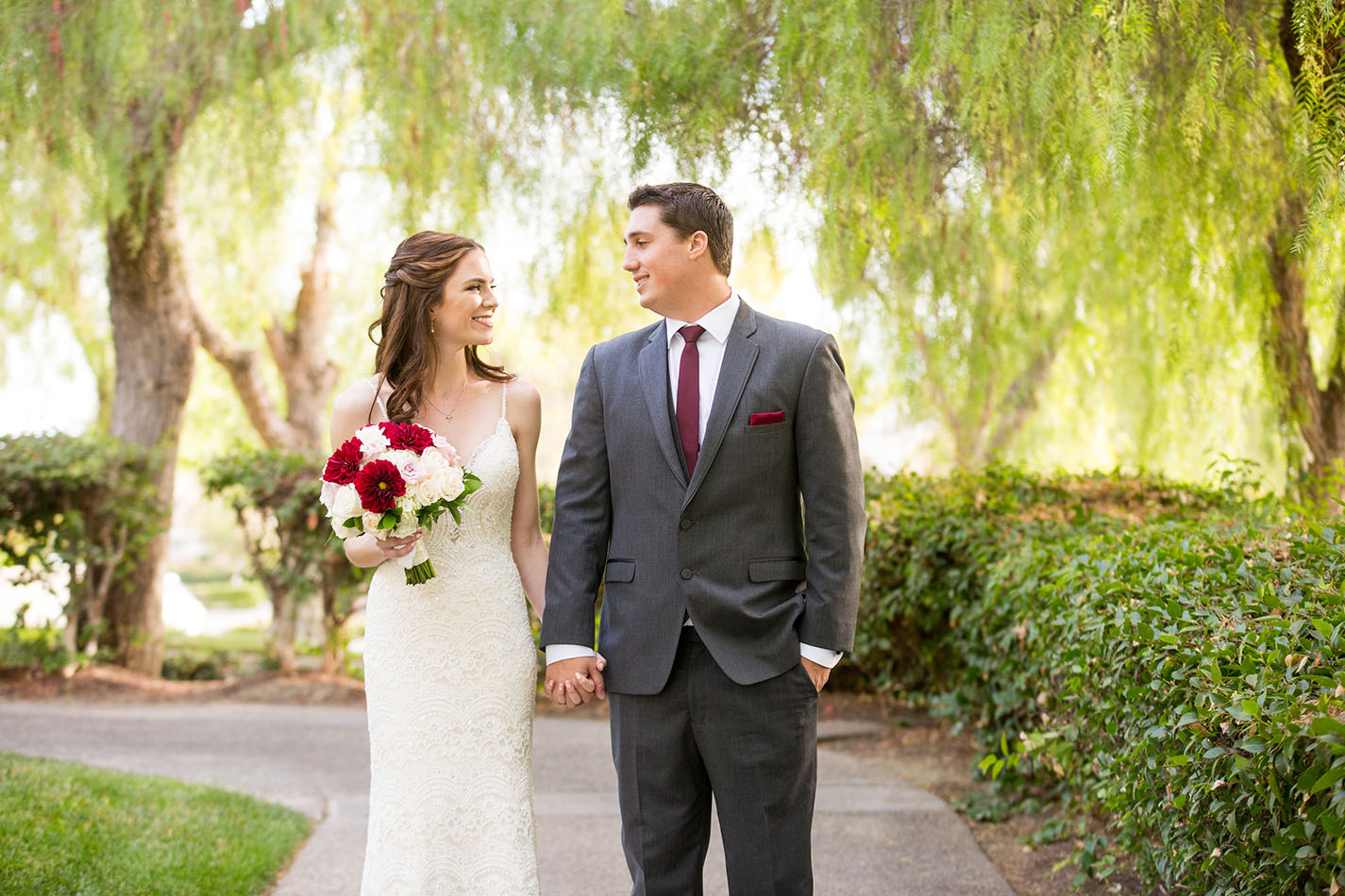 The property features shady weeping willow trees, lush greens, and flower gardens for a romantic setting