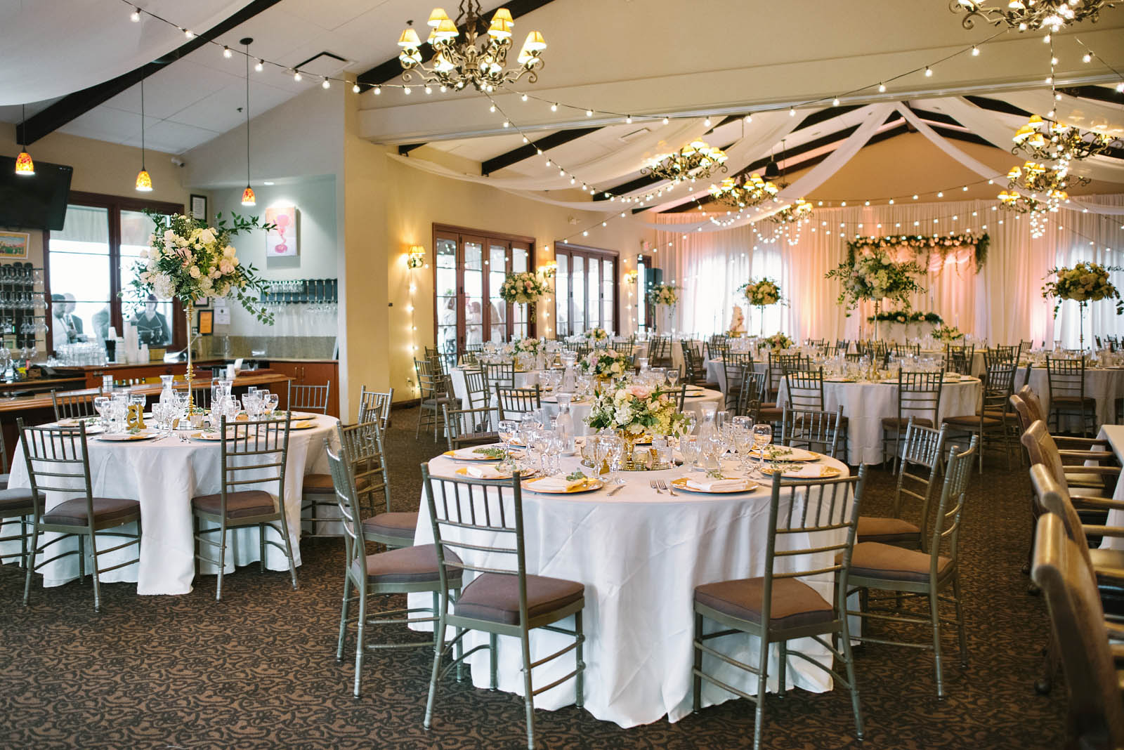 Your wedding reception features gorgeous twinkle lights, draping backdrop, chandeliers, and exclusive access to your private bar.