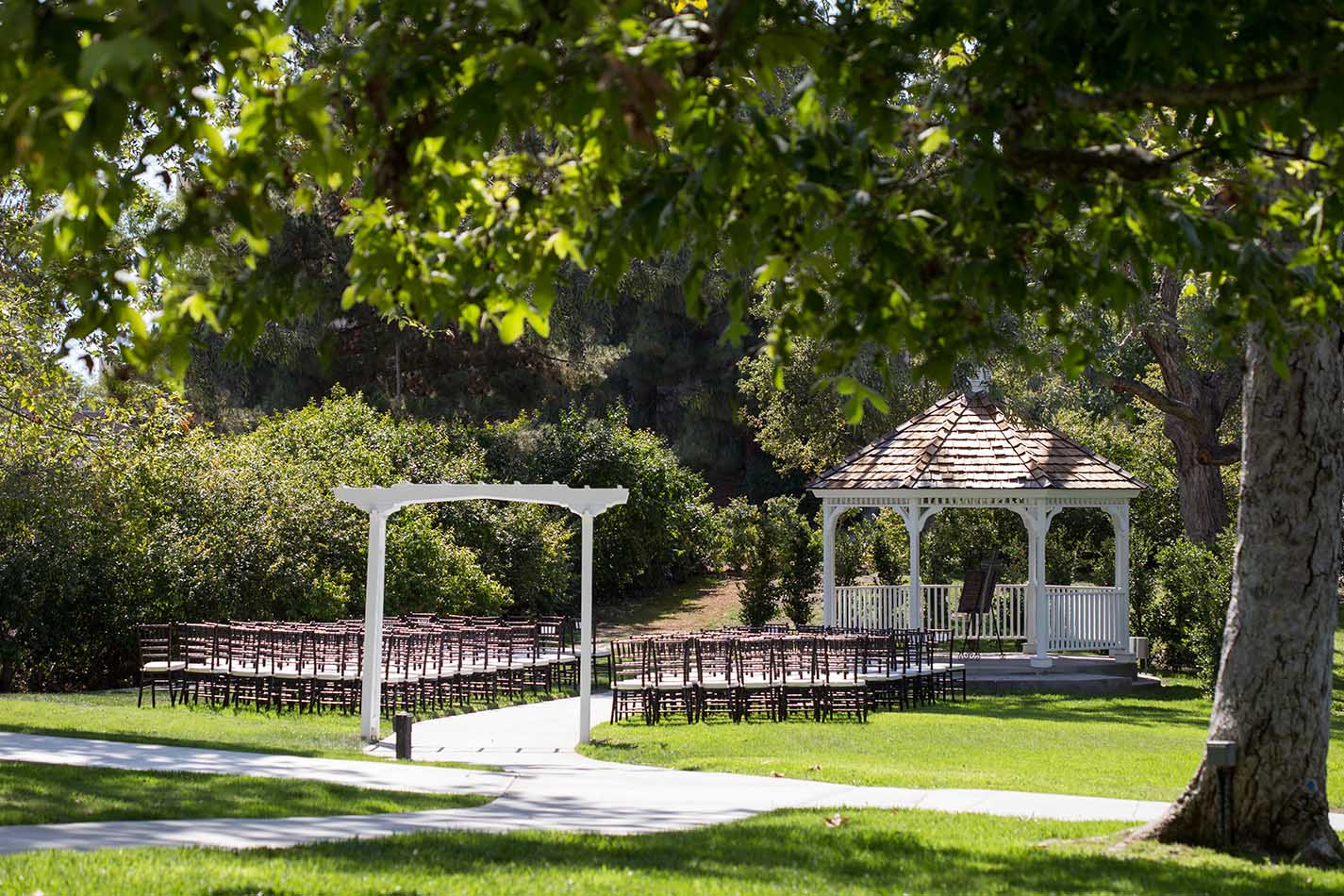 Surrounded by expansive views of lush greens and twinkling tree lights, you'll make your way to your scenic ceremony.