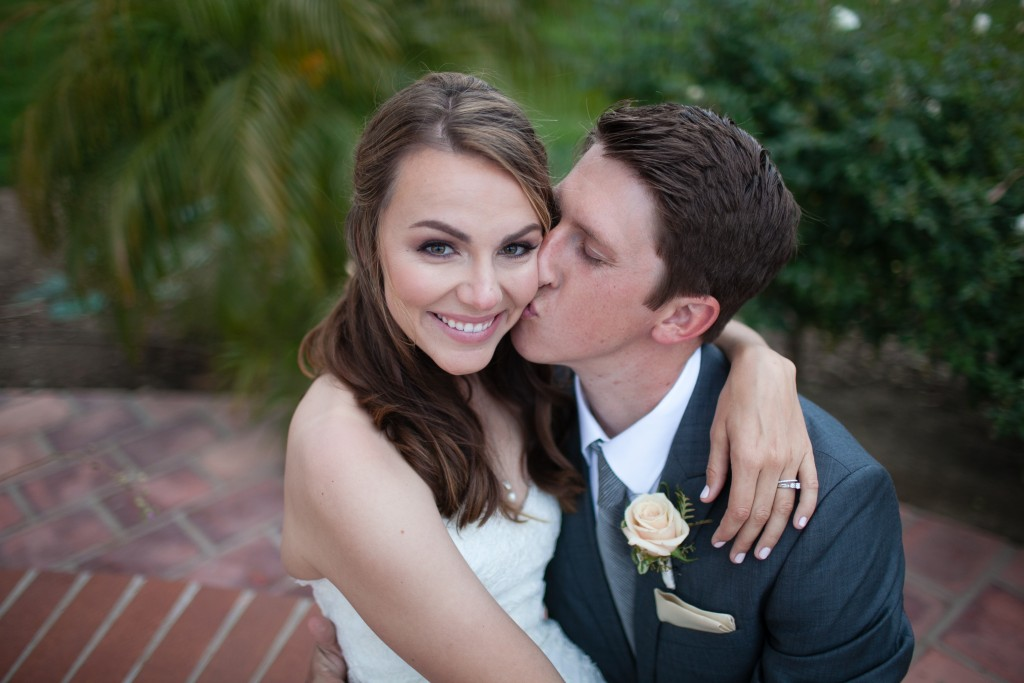 beautiful shot of bride and groom with groom kissing her cheek
