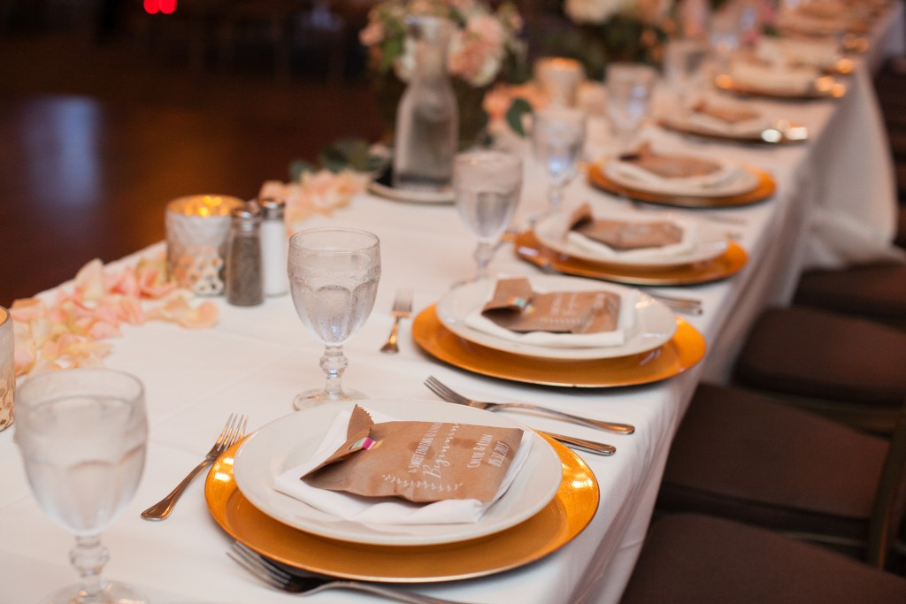 sweetheart table set with gorgeous place settings and wedding favors