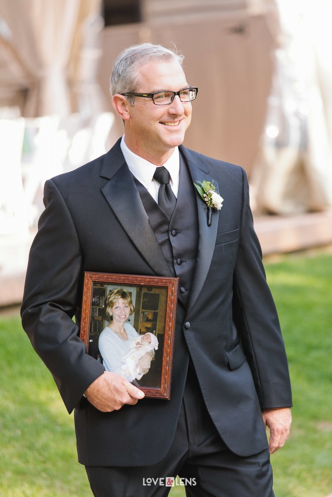 groomsman holding picture of mother