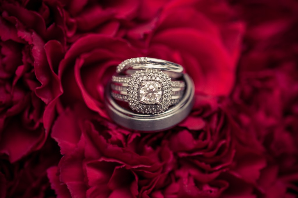 bride and groom rings on red flowers