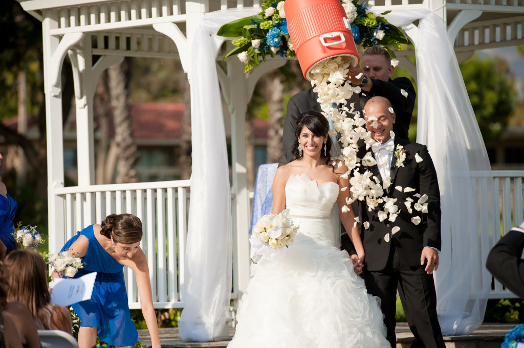 bride and groom with rose petals poured out of a sports drink container