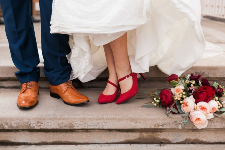 bride's red heels for wedding with bouquet and groom's shoes