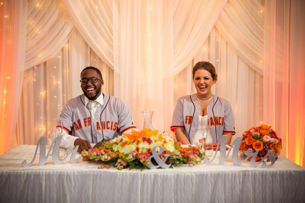 bride and groom at reception wearing their favorite sports team