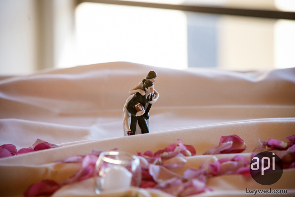 cake topper with groom holding a football for a sports wedding theme