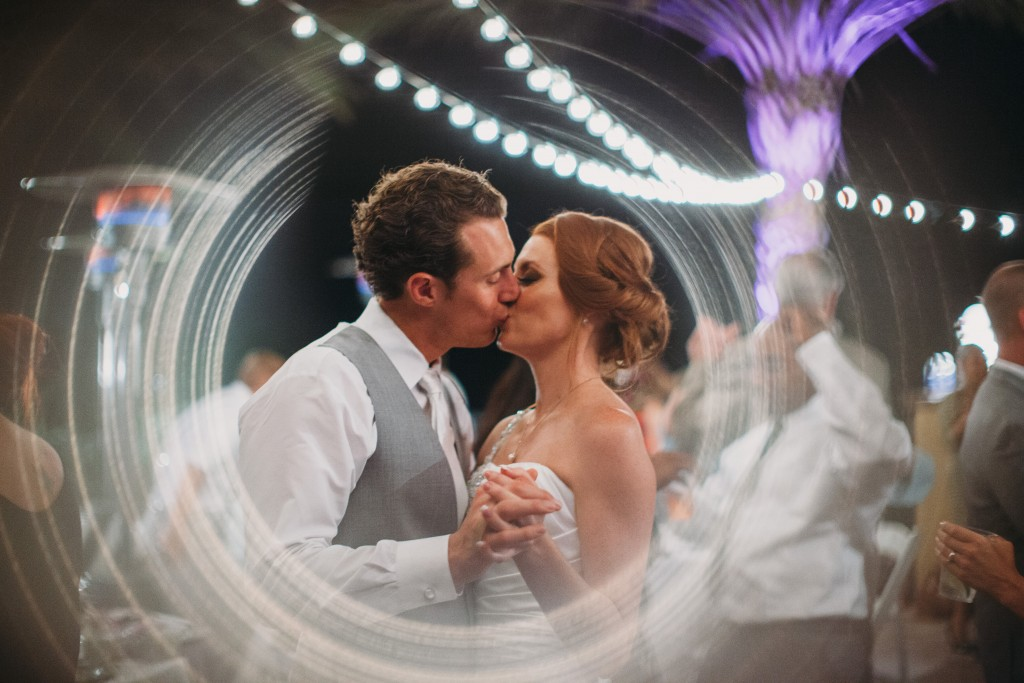 bride and groom kissing under hanging lights