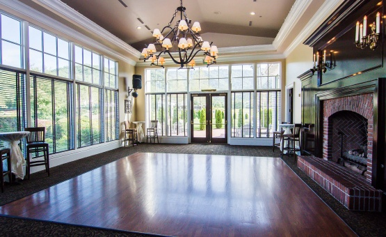 A grand fireplace and floor to ceiling windows