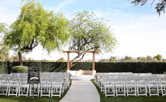 Newly renovated ceremony site with wooden arch and privacy fence