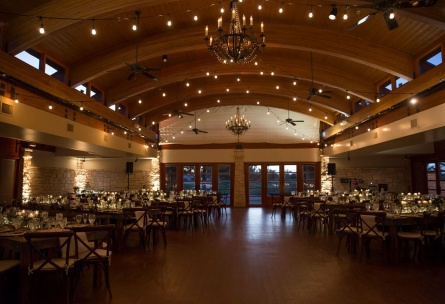 Dramatic indoor wedding reception with cross-back chairs.