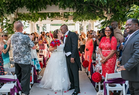 Newlyweds kiss as their guests look on - Jefferson Street Mansion - Benicia, California - Solano County - Wedgewood Weddings